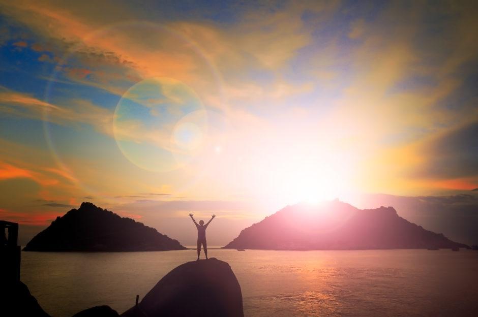 腕を上げて島の後ろに夕日を持つ男