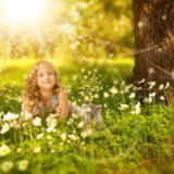 お花畑で日光を浴びる女の子