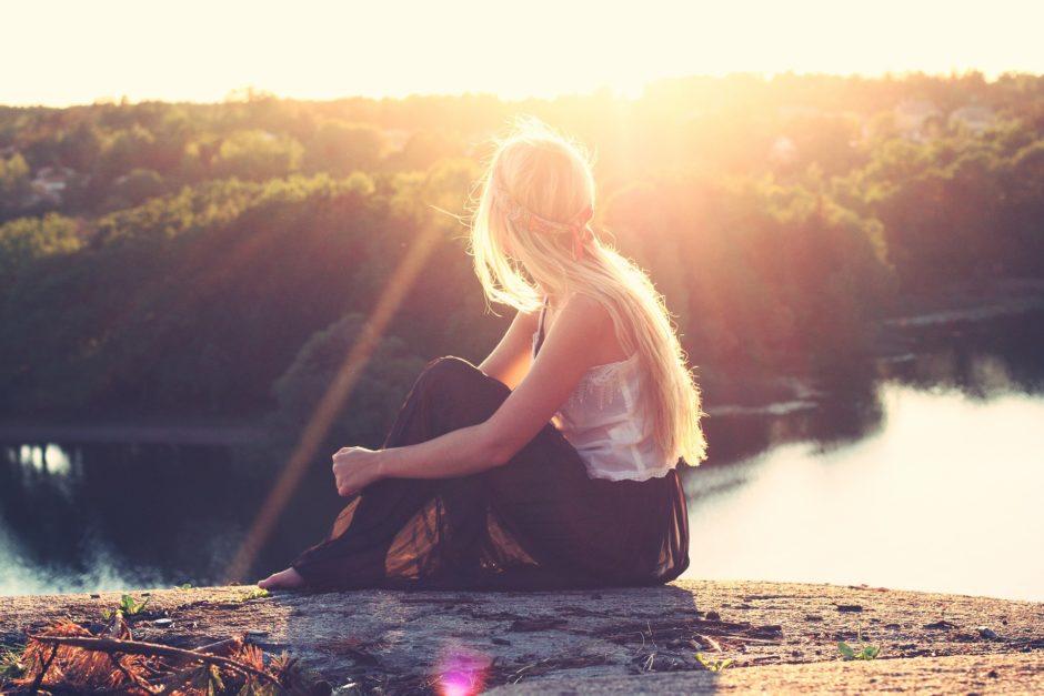太陽を見て座っている女性