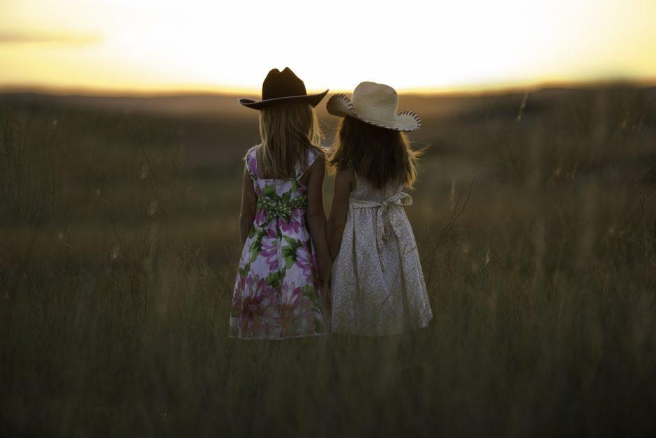 草原で手を繋ぐ姉妹