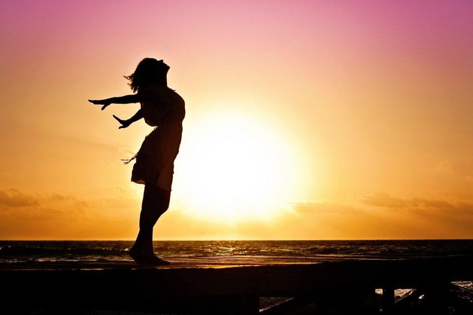 夕陽の前で喜ぶ女性